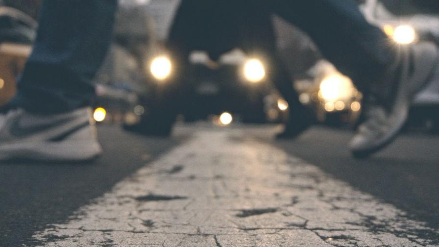 Image décorative de personnes marchant le long d'un passage pour piétons avec des voitures arrêtées à l'arrière-plan.