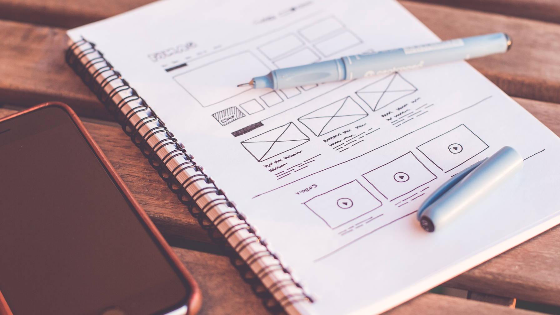 Téléphone sur un bureau à côté d'un stylo et d'un ordinateur portable avec une mise en page de conception Web dessinée dessus.