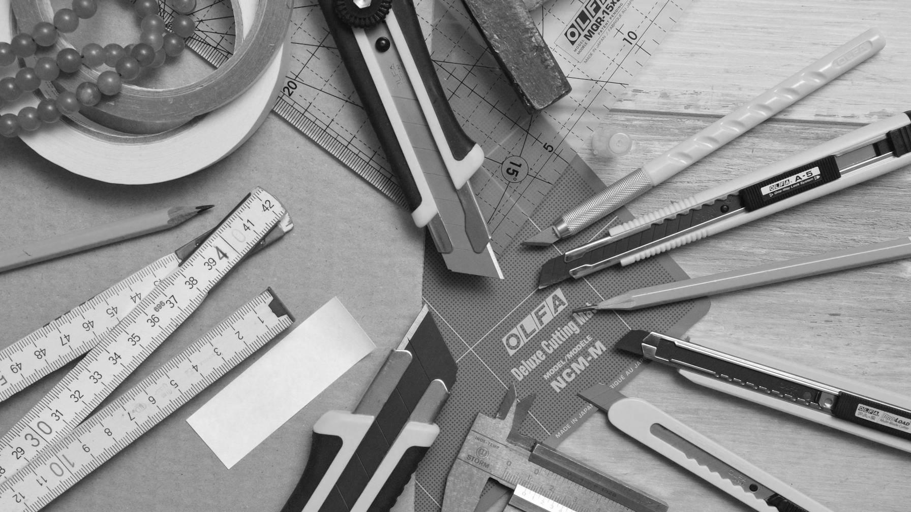 Règles, mesureurs de ruban, coupe-boîtes et crayons sur un bureau.
