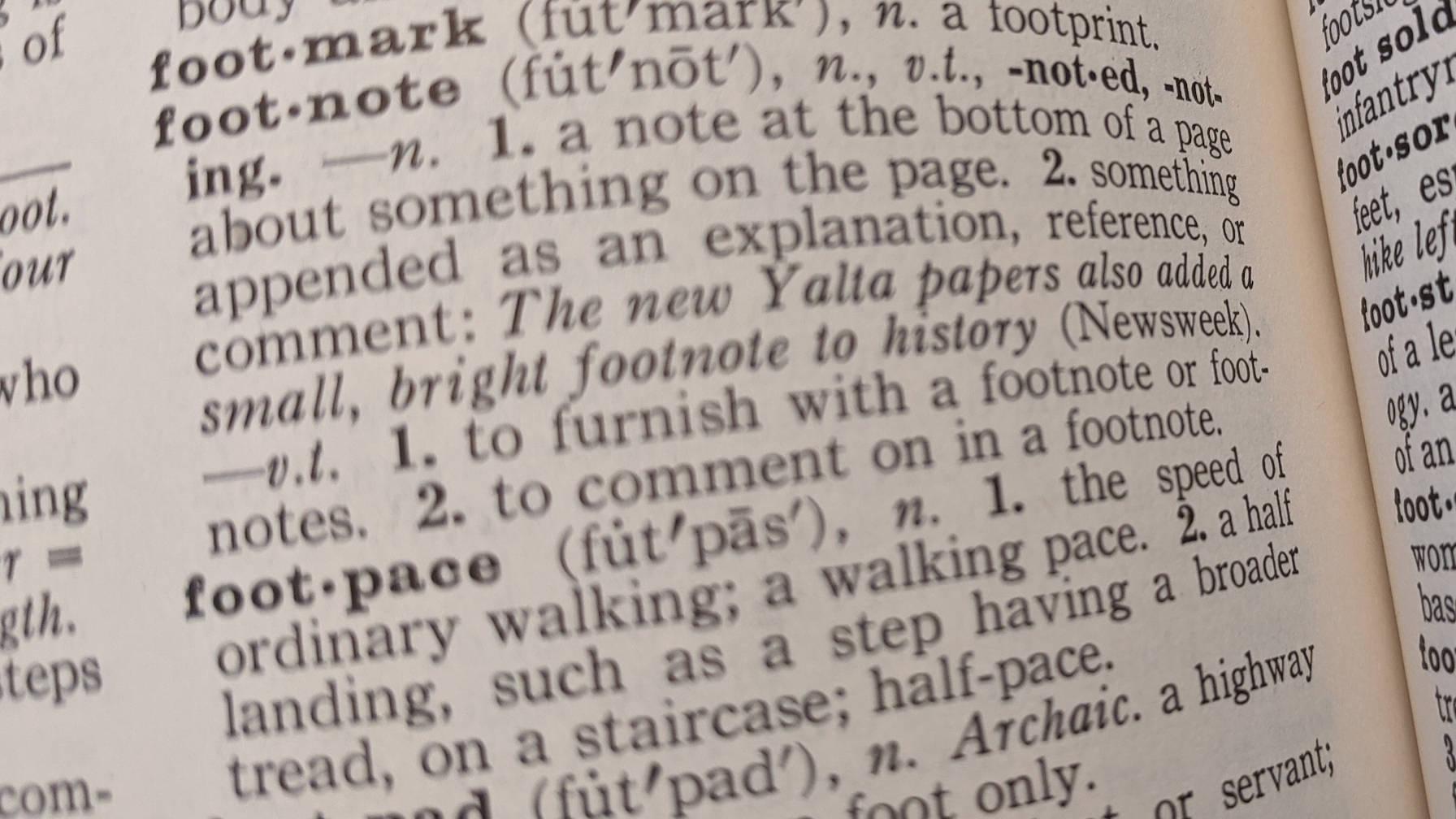 """Image décorative d'une page dans un dictionnaire, mettant en évidence le """"note de bas de page"""" définition."""