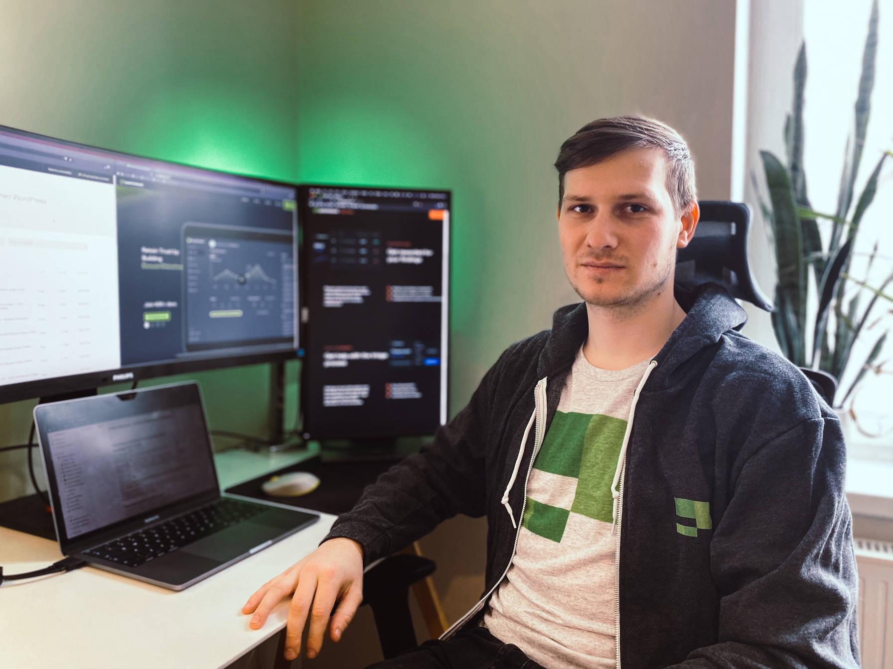 Le fondateur et PDG de Patchstack, Oliver Sild, assis à un bureau avec un ordinateur portable et des moniteurs.